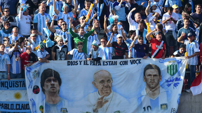 Fans of the Argentina national side display their reverence for Diego Maradona, Pope Francis and Lionel Messi