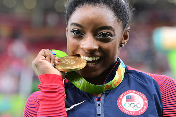 TOPSHOT - US gymnast Simone Biles celebrates with her gold medal after the women's individual all-around final of the Artistic Gymnastics at the Olympic Arena during the Rio 2016 Olympic Games in Rio de Janeiro on August 11, 2016. US gymnast Simone Biles won the event ahead of her compatiot Alexandra Raisman and Russia's Aliya Mustafina. / AFP / Emmanuel DUNAND        (Photo credit should read EMMANUEL DUNAND/AFP/Getty Images)