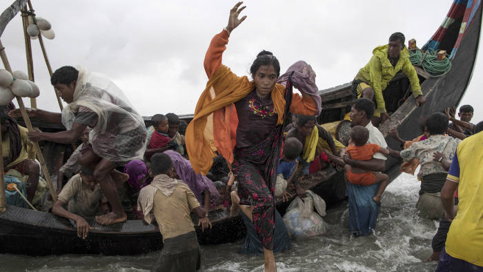 DAKHINPARA, BANGLADESH - SEPTEMBER 12: Rohingya refugees jump from a wooden boat as it begins to tip over after travelling from Myanmar, on September 12, 2017 in Dakhinpara, Bangladesh. Recent reports have suggested that around 290,000 Rohingya have now fled Myanmar after violence erupted in Rakhine state. The 'Muslim insurgents of the Arakan Rohingya Salvation Army' have issued statement that indicates that they are to observe a cease fire, and have asked the Myanmar government to reciprocate. (Photo by Dan Kitwood/Getty Images)