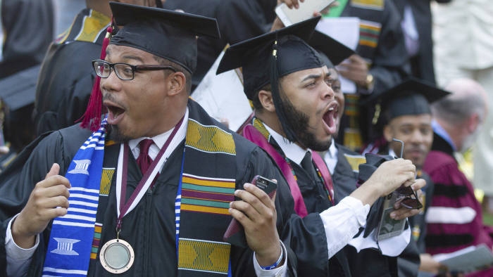 Graduates react after hearing billionaire technology investor and philanthropist Robert F. Smith say he will provide grants to wipe out the student debt of the entire 2019 graduating class at Morehouse College in Atlanta, Sunday, May 19, 2019. (Steve Schaefer/Atlanta Journal-Constitution via AP)