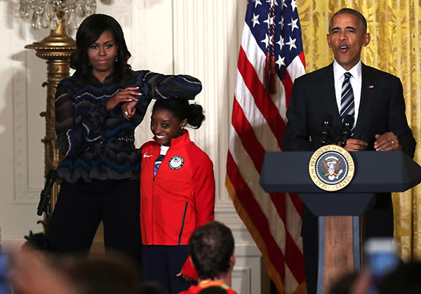 WASHINGTON, DC - SEPTEMBER 29:  U.S. first lady Michelle Obama(L) rests her elbow on the head of Olympian Simone Biles (2nd L) as President Barack Obama (R) speaks during an East Room event at the White House September 29, 2016 in Washington, DC. President Obama and the first lady welcome the 2016 U.S. Olympic and Paralympic teams to the White House to honour their participation and success in the Rio Olympic Games this year.  (Photo by Alex Wong/Getty Images)