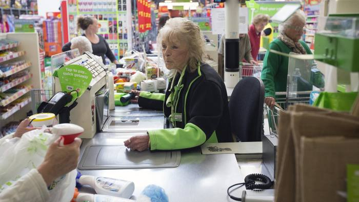 An employee scans a customer's purchases through a till at a check-out desk inside an Asda supermarket, the U.K. retail arm of Wal-Mart Stores Inc., in Watford, U.K., on Thursday, Oct. 17, 2013.