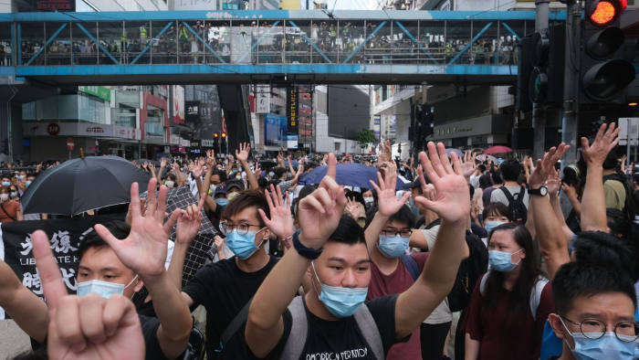 """Demonstrators gesture the """"Five demands, not one less"""" protest motto during a protest in Hong Kong, China, on Wednesday, July 1, 2020. Hong Kong wokeup toa new reality on Wednesday, after China began enforcing a sweeping security law that could reshape the financial hub's character 23 years after it took control of the former British colony. Photographer: Roy Liu/Bloomberg"""