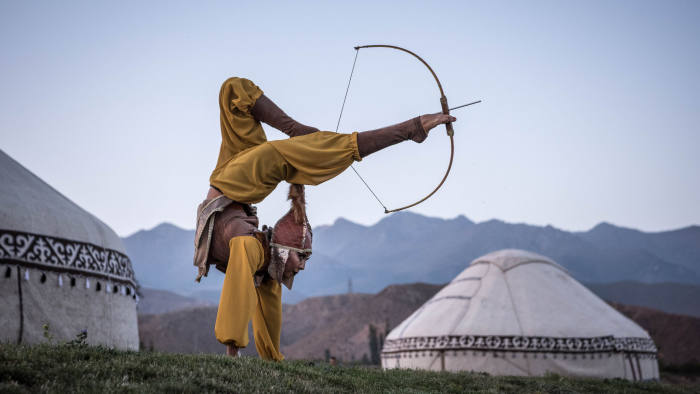 """Aida Akmatova, a circus performer, shoots a bow and arrow with her feet at the World Nomad Games in Cholpon-ata, Kyrgyzstan, Sept. 4, 2018. Local participants reveled in the events; Akmatova also competed in horseback archery. """"This is not just another performance, but a key event in my life,"""" she said. """"I can help pass down our culture, our traditions."""" (Sergey Ponomarev/The New York Times) Credit: New York Times / Redux / eyevine For further information please contact eyevine tel: +44 (0) 20 8709 8709 e-mail: info@eyevine.com www.eyevine.com"""