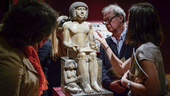 Members of the public and gallery staff examine The Northampton Sekhemka, an Egyptian painted limestone statue of Sekhemka, Inspector of the Scribes, at Christie's auction house in central London on June 13, 2014. The statue is going to auction on July 10, 2014 with an expected reserve of 4-6 million GPD (5-7 million Euros, 7-10 million USD). AFP PHOTO / LEON NEAL (Photo credit should read LEON NEAL/AFP/Getty Images)