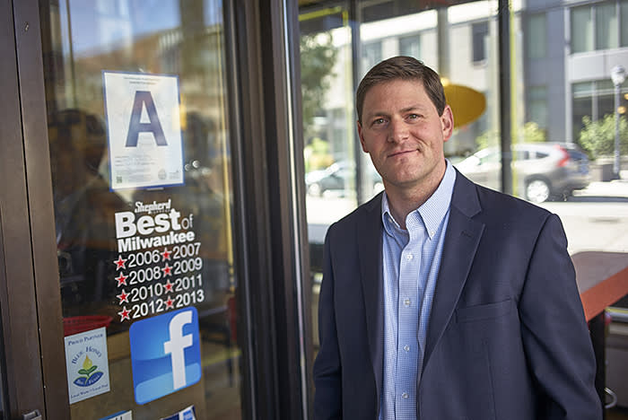 Andrew Lochowicz an EMBA student who helped create the algorithm that powers Milwaukee's new restaurant grading system poses next to the grading system in front of restaurants Wednesday, Oct. 9, 2019, in Milwaukee. (Darren Hauck for The Financial Times)