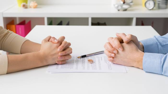 Couple going through divorce signing papers