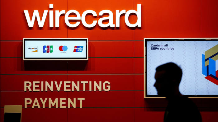 FILE PHOTO: A man walks past the Wirecard booth at the computer games fair Gamescom in Cologne, Germany, August 22, 2018. REUTERS/Wolfgang Rattay/File Photo