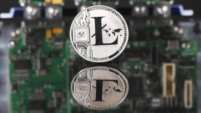 A coin representing Litecoin cryptocurrency sits reflected on a polished surface and photographed against a computer circuit board in this arranged photograph in London, U.K., on Thursday, Feb. 8, 2018. Cryptocurrencies tracked by Coinmarketcap.com have lost more than $500 billion of market value since early January as governments clamped down, credit-card issuers halted purchases and investors grew increasingly concerned that last year's meteoric rise in digital assets was unjustified. Photographer: Luke MacGregor/Bloomberg