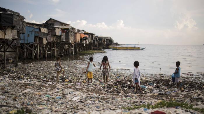 This photo taken on May 9, 2018 shows children walking on garbage filled bay in Manila. (Photo by NOEL CELIS / AFP) (Photo credit should read NOEL CELIS/AFP via Getty Images)