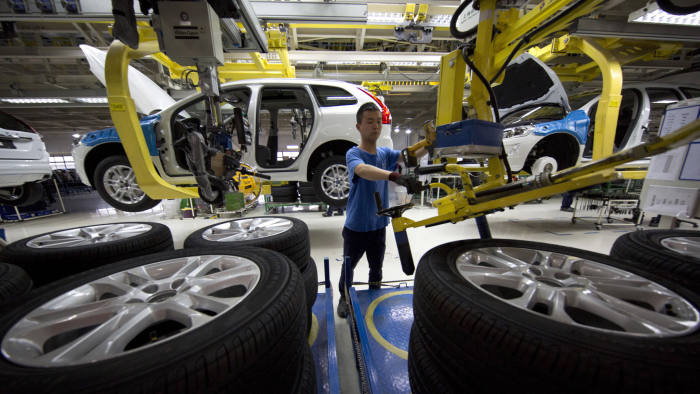 """In this photo taken Tuesday, April 21, 2015, a worker installs wheels on a car at a Volvo factory in Chengdu in southwestern China's Sichuan province. On the verge of exporting the first """"Made in China"""" cars to the United States, Volvo is determined to show they are as good as vehicles it produces in Europe. (AP Photo/Ng Han Guan)"""