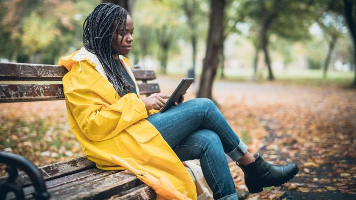 Young woman with yellow raincoat enjoying in the autumn park, using digital tablet