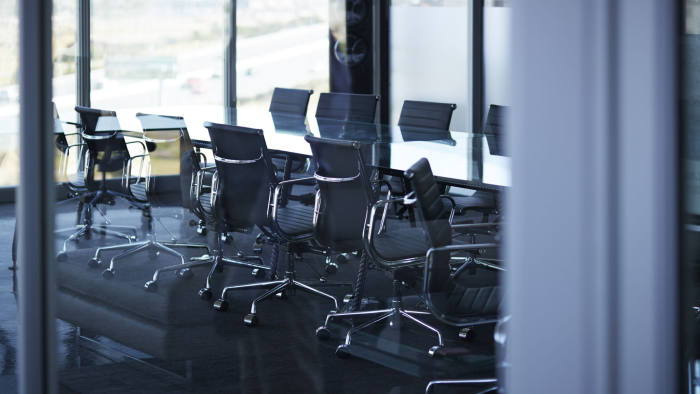 Empty chairs in large conference room, in modern office space with glass walls