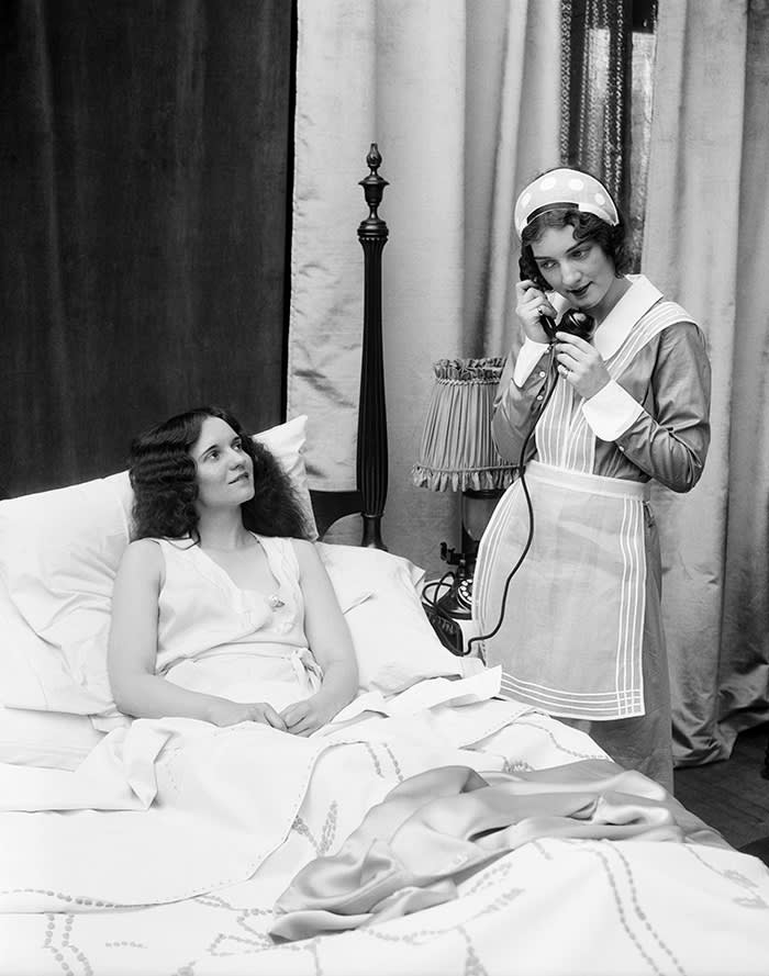 Two women in bedroom: one dressed as a maid on the phone, the other in bed smiling up at the maid