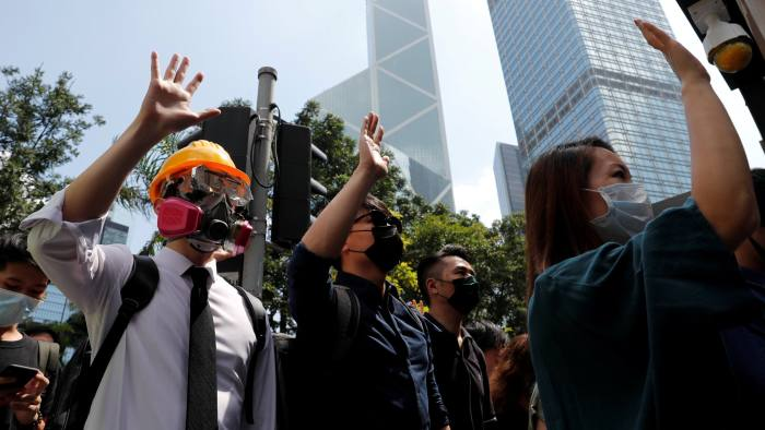 FILE PHOTO: Anti-government office workers wearing masks attend a lunch time protest, after local media reported on an expected ban on face masks under emergency law, at Central, in Hong Kong, China, October 4, 2019. Cheung Kong Center can be seen at right in the background. REUTERS/Tyrone Siu/File Photo To match Special Report HONGKONG-PROTESTS/TYCOONS