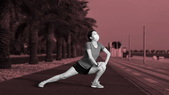 Asian woman exercising and stretching while wearing protective surgical mask to warm up before fitness workout outdoors