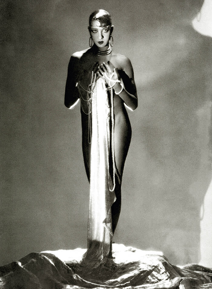 Dancer Josephine Baker, standing nude, with a long piece of fabric draped in front of her hanging from long stands of pearls which are wrapped around her hands. (Photo byGeorge Hoyningen-Huene/Condé Nast via Getty Images)