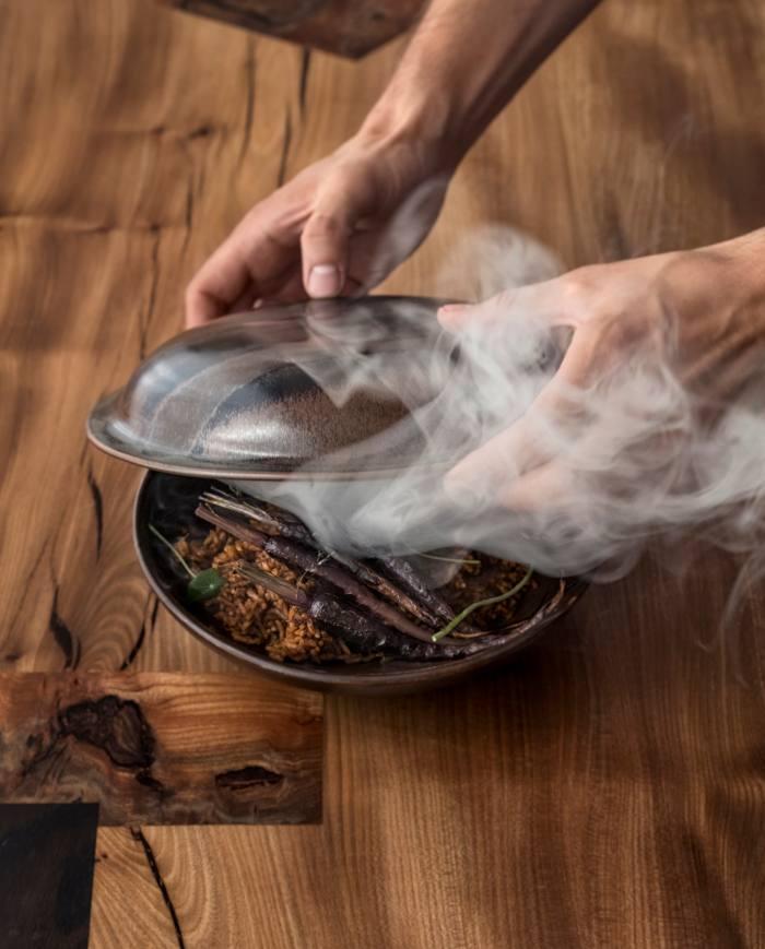 Smoked Jollof Rice at Ikoyi, served withaged sheep kebab, crab custard or flame beets