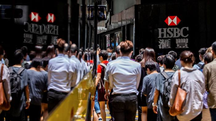Pedestrians walk past the logo for HSBC outside a local branch bank in Hong Kong