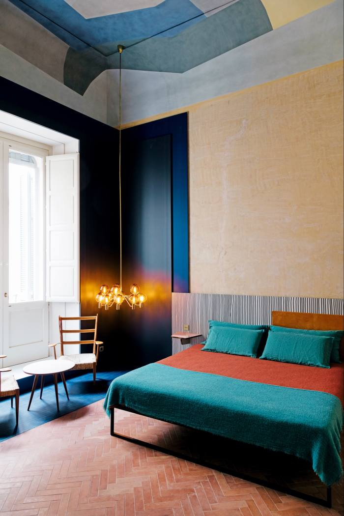 A bedroom with a 1960s ceiling lamp by Hans-Agne Jakobsson, a 1957 Gio Ponti table and 1930s chairs by Italian architect/designer Pier Giulio Magistretti
