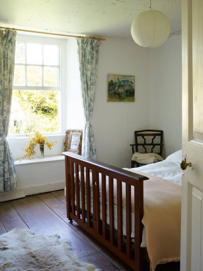 A guest bedroom with a painting sketch of Luscombe, c1962, and an ink drawing of an oak tree, c1978, both by David