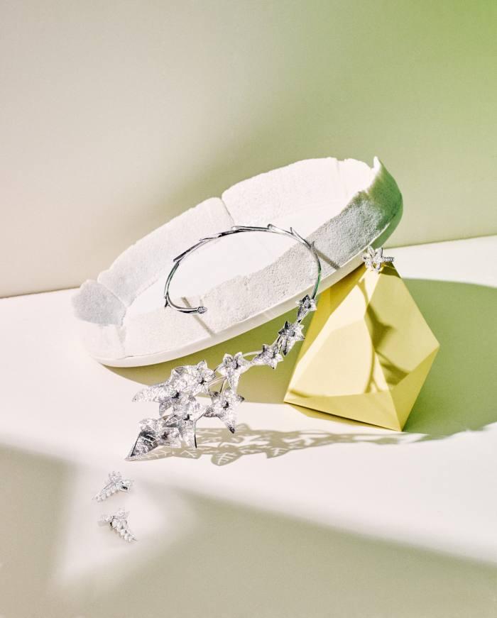 From left: Chaumet white‑gold and diamond Joséphine Valse Impériale earrings. Boucheron white-gold and diamond Lierre de Paris necklace. De Beers white-gold and diamond Blooming Lotus ring