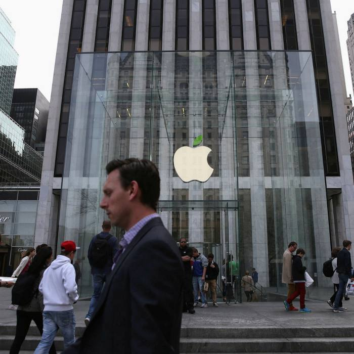 People walk past an Apple store in New York. The group plans to cut itsmissions by 75% by 2030 across its entire supply chain