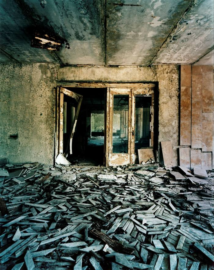 In an abandoned building, grey pieces of a wooden floor are piled up irregularly in front of a rusty door