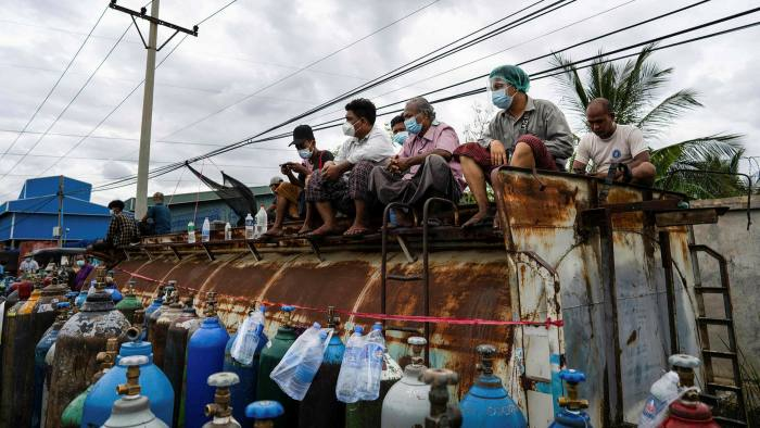 People wait to fill up empty oxygen canisters outside a factory in Mandalay, Myanmar