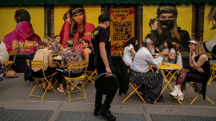An employee assists customers sitting in the outdoor dining area of a restaurant in New York
