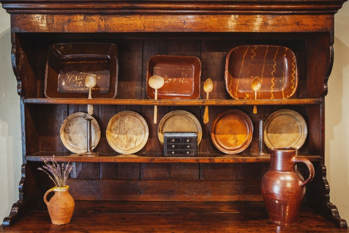 """An 18th-century Welsh oak dresser, £7,250. Top shelf: Welsh Buckley-pottery slipware dishes, from £350. Middle shelf: five 19th-century sycamore plates, from £265 each, a pair of Welsh tin """"hog-scraper"""" candlesticks, £395, and a miniature 19th-century slate model of a bureau, £225. Bottom shelf, from left: a small 19th-century earthenware jug, £350, and a 19th-century stoneware jug, £475"""