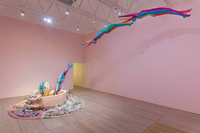 Multicoloured human figures fly through the room into a vat