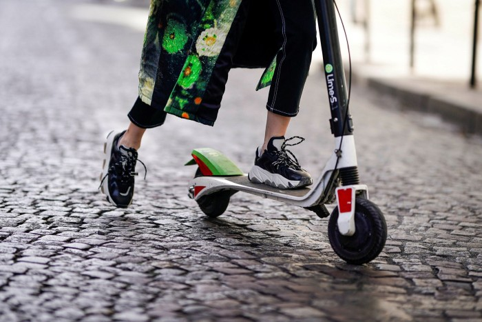 PARIS, FRANCE - SEPTEMBER 29:  Caroline Daur wears a green printed coat, sneakers, sunglasses, a Prada bag, and is using a Lime-S electric scooter from the bike sharing service company 'Lime',