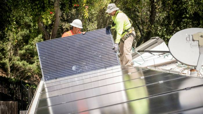 PetersenDean Inc. employees install solar panels on the roof of a home