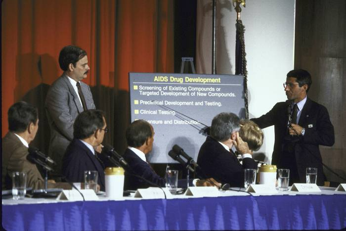 Fauci (right) lectures to the President's Commission on Aids in 1987, with Ronald Reagan on the far left