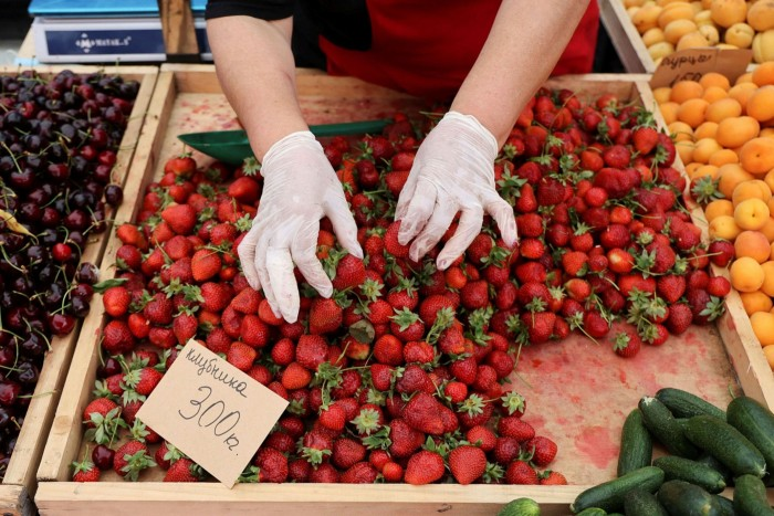 A woman sorts strawberries on a market stall in Kashira, a Russian town