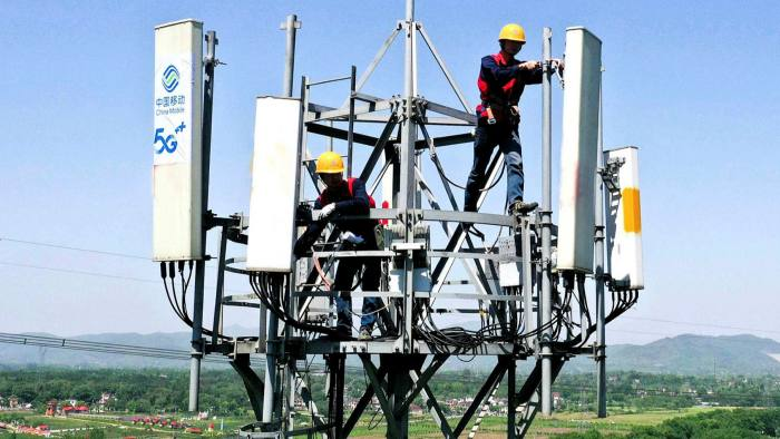 China Mobile workers maintain a communication tower stuck with a 5G symbol, near a tourist site