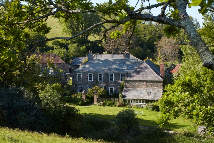 The house is a former dairy farm in a steep south Devon valley