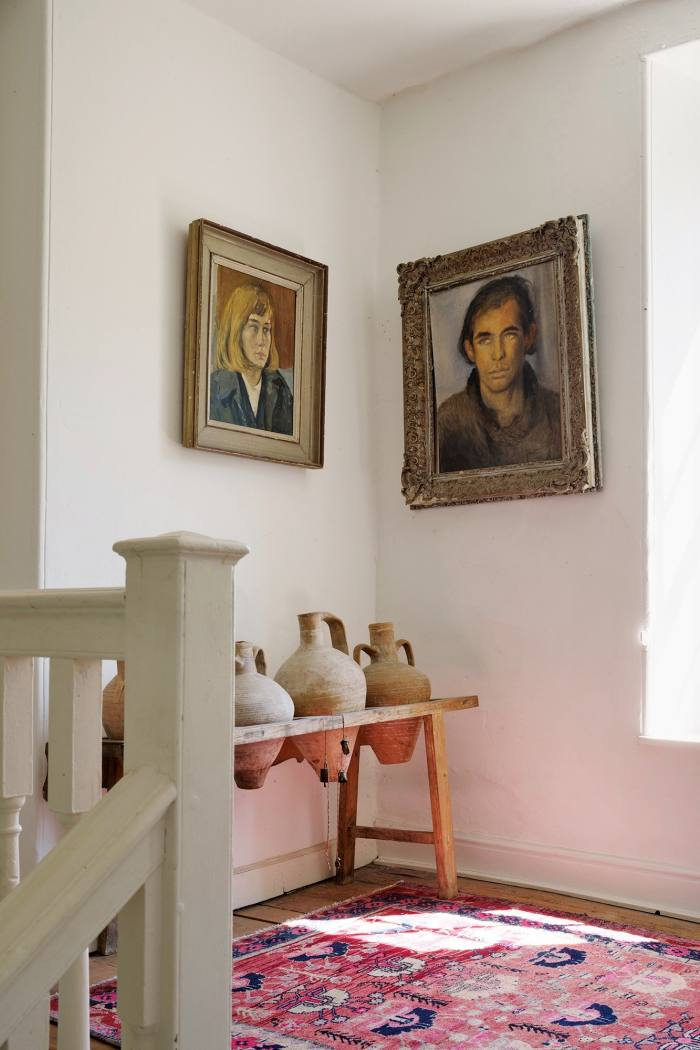 Portraits of Yasmin – by Ronald Ossory Dunlop – and Julian David, above a row of old terracotta pots
