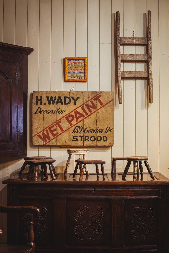 """An early-20th-century """"Wet Paint"""" sign, £575. Above it is a small Welsh sampler dated 1873, £350, and a rare Welsh hand-barrow, £345. Small 19th-century Welsh stools and candle stands, from £135, stand on a carved 17th-century Welsh oak chest, £1,680"""