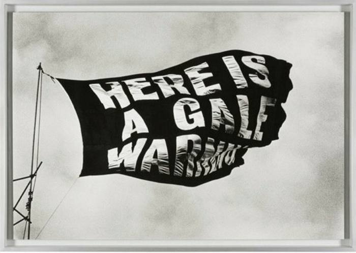 A black and white photo of a black flag waving. It has white writing reading: here is a gale warning