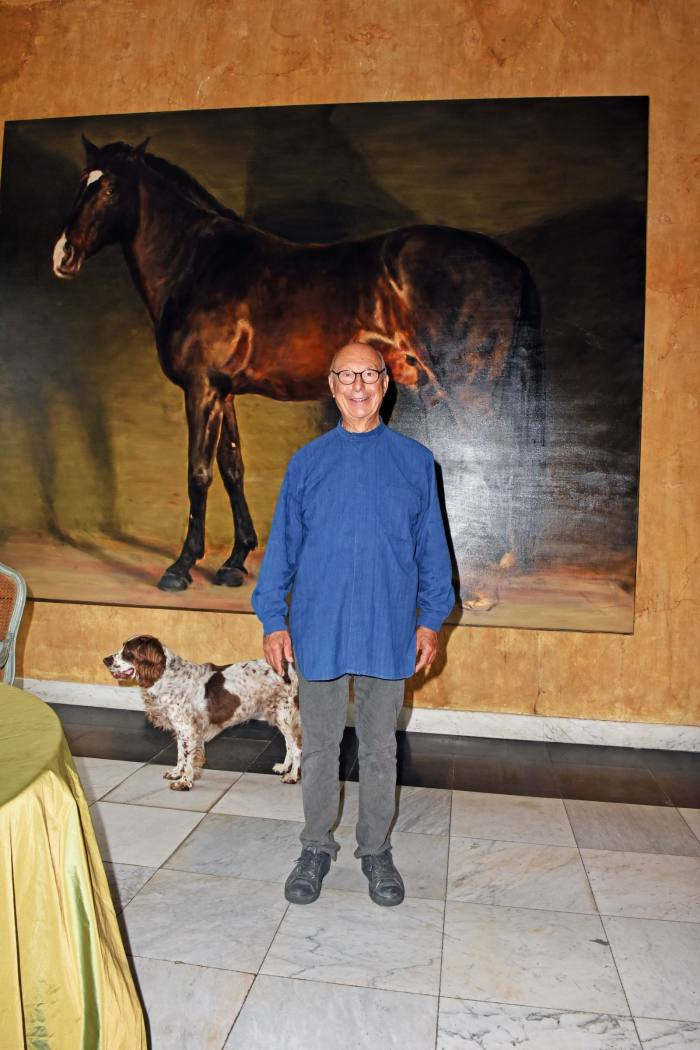 """Axel Vervoordt, pictured at home in 's-Gravenwezel with his springer spaniel Inu, has such affection for his former horse Raio (who died this year), he had him captured in a painting by the artist Michaël Borremans. Now in his 70s, the Belgian designer is still a keen rider. """"I love horses – my father was a horse dealer,"""" he says of his regular gallops, which take him across his 62-acre estate."""