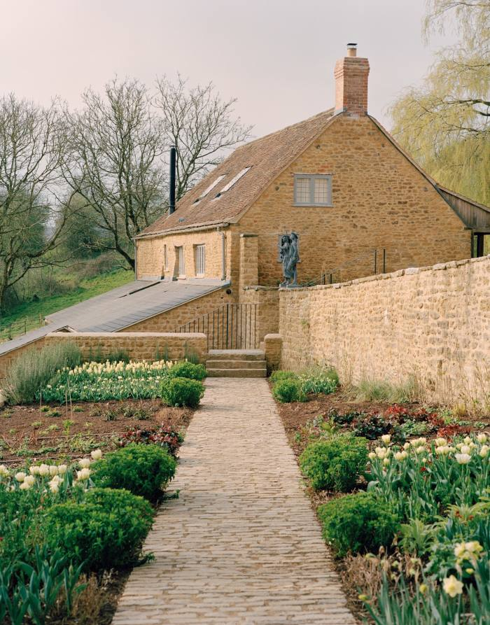 A path through daffodil and tulip beds leading to the Cheese Barn