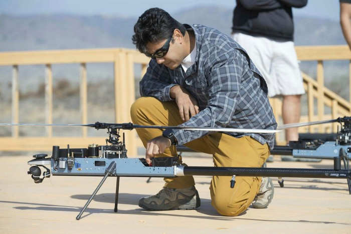An Anduril Industries engineer checks a heli-drone before it takes off from a Marine Corps base in California