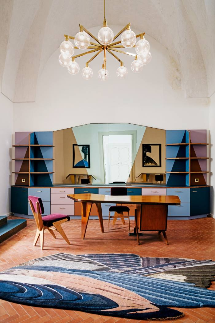 The reception area features a coloured-mirror Martino Gamper cabinet, as well as 1950s chairs and desk by Brazilian architect/designer José Zanine Caldas, a 1960 ceiling light by by Hans-Agne Jakobsson and a Feathers Freeform Big rug by Maarten De Ceulaer for CC-Tapis