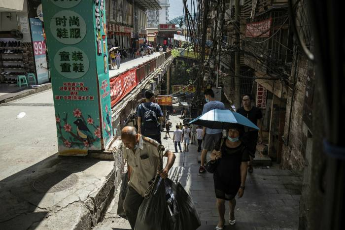 Pedestrians walk through the Chaotianmen Docks area of Chongqing. Official data show China's urban residents reported a 2 per cent drop in per capita disposable income in the first half of the year