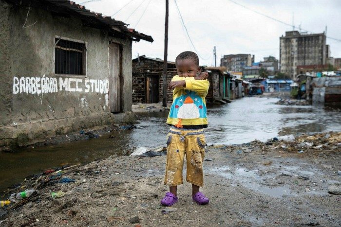 Rising waters behind a child in Beira, Mozambique. Younger generations are pushing for changes on climate policy