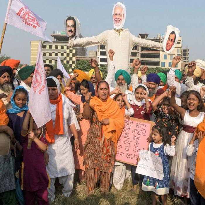 Farmers and their children shout slogans before burning effigies of Narendra Modi (C), Reliance Industries chairman Mukesh Ambani (R) and Gautam Adani following the recent passing of agriculture bills in parliament, in Amritsar