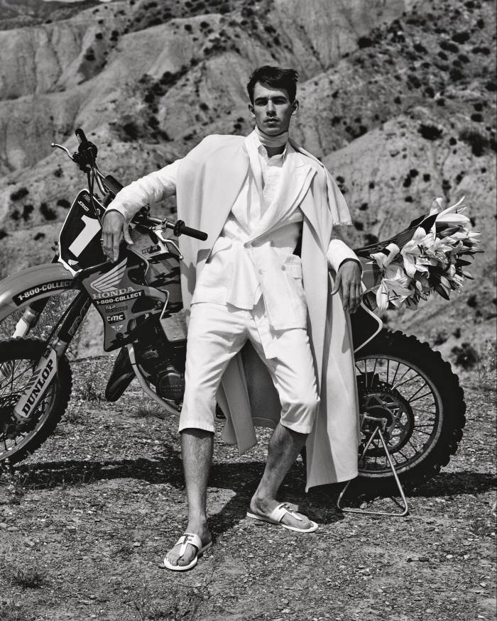 Kappe by Federica Bonifaci wooldouble crepe cape, £850. Dolce & Gabbana linen jacket, £2,050, and cotton drill trousers, £465. Ralph Lauren Purple Label poplin tuxedo shirt, £540. Tom Ford leather and brass Brighton sandals, £690. Vintage silkscarf, stylist's own. Ring, model's own