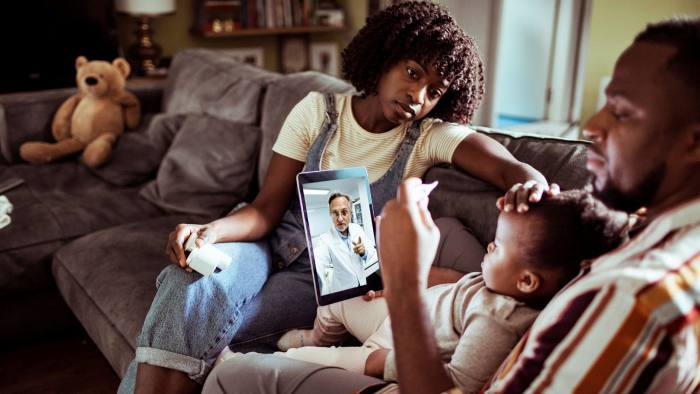 How we live now: lockdown has ended personal contact with professional advisers, from doctors to lawyers. Close-up of a young family consulting with their doctor over a digital tablet